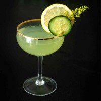 A cocktail in a coup glass, garnished with a cucumber slice, lemon, and wispy flower on a table.