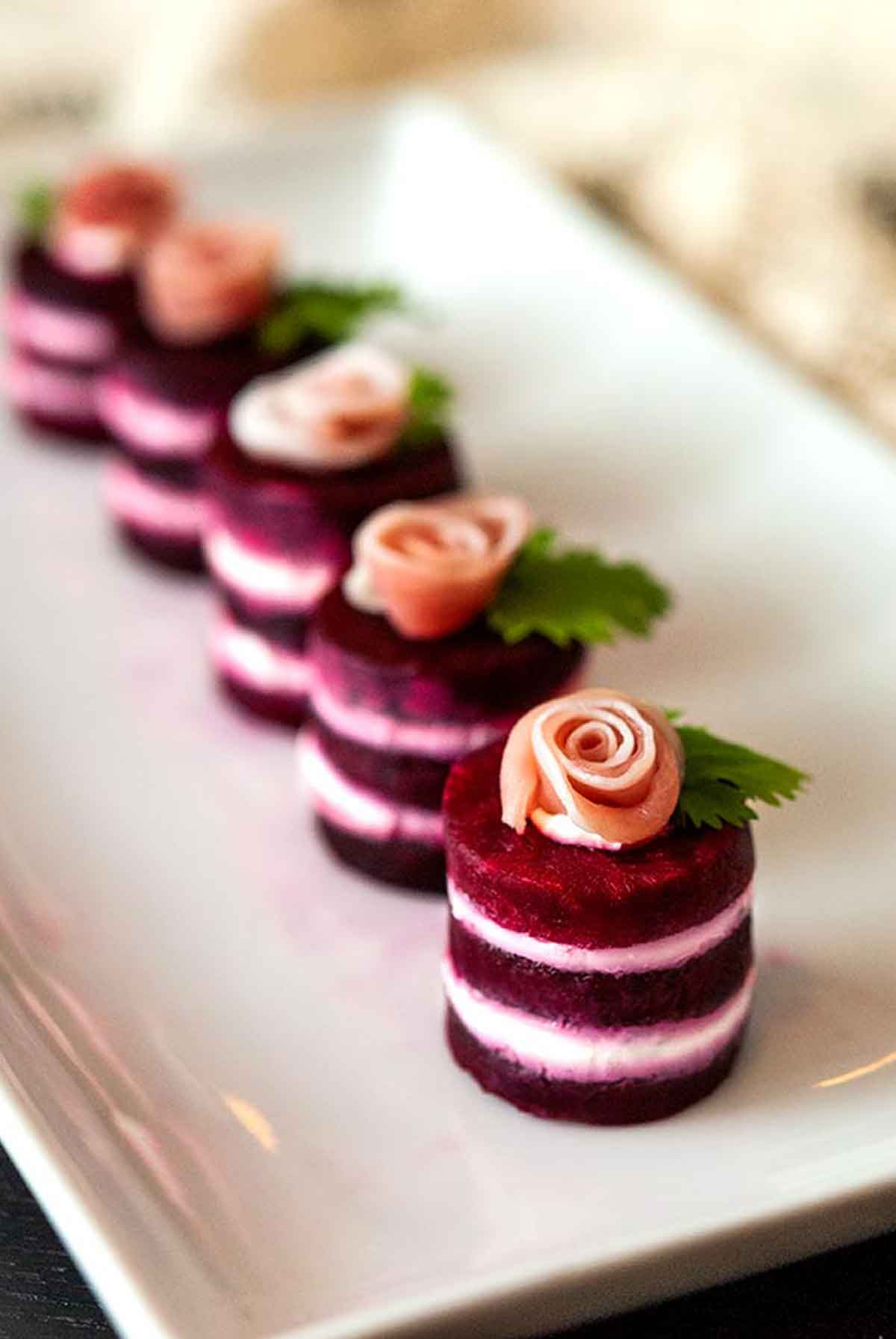 6 beet napoleons, with prosciutto roses on top, garnished with cilantro leaves on a plate.