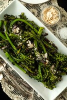 A plate of sautéed broccoli rabe on a lace tablecloth, beside 2 small bowls of garnish and 2 antique forks.