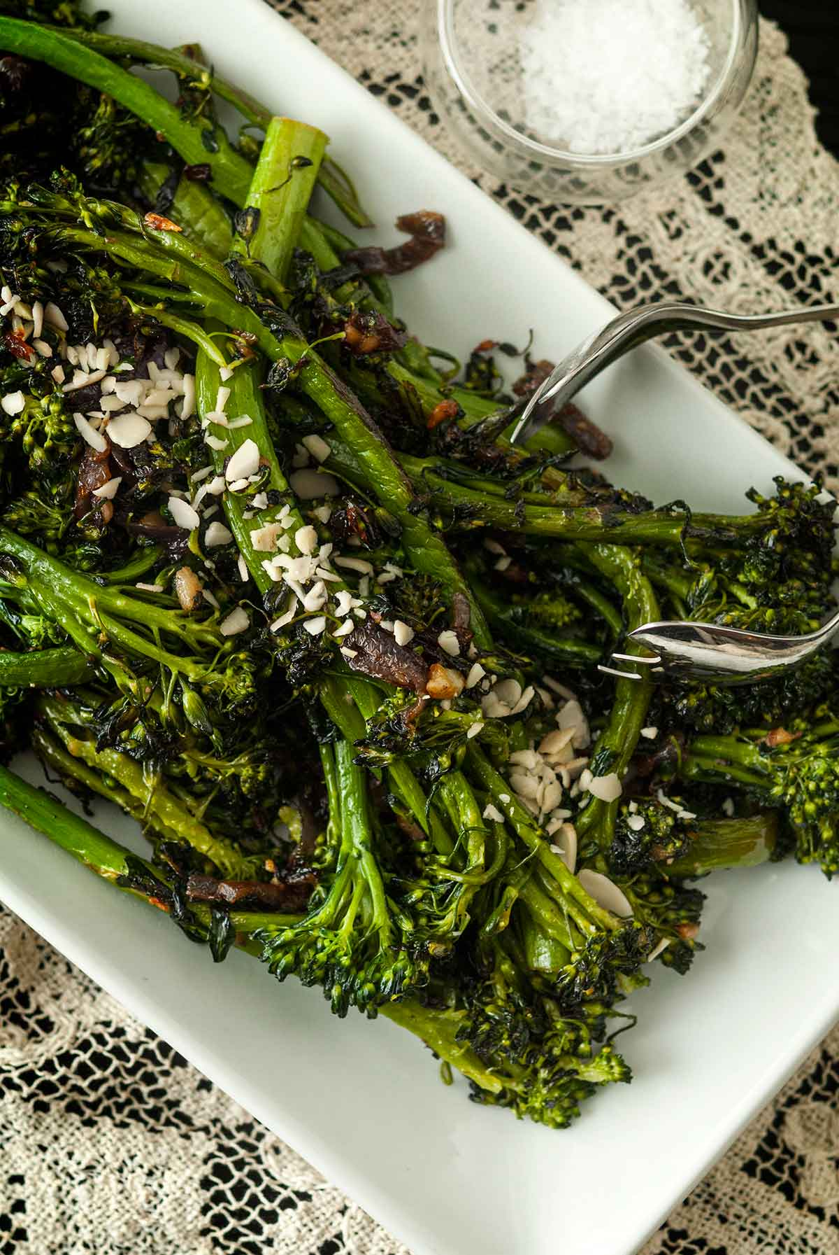 A plate of sautéed broccoli rabe on a lace tablecloth, beside a small bowl of salt, with salad tongs.