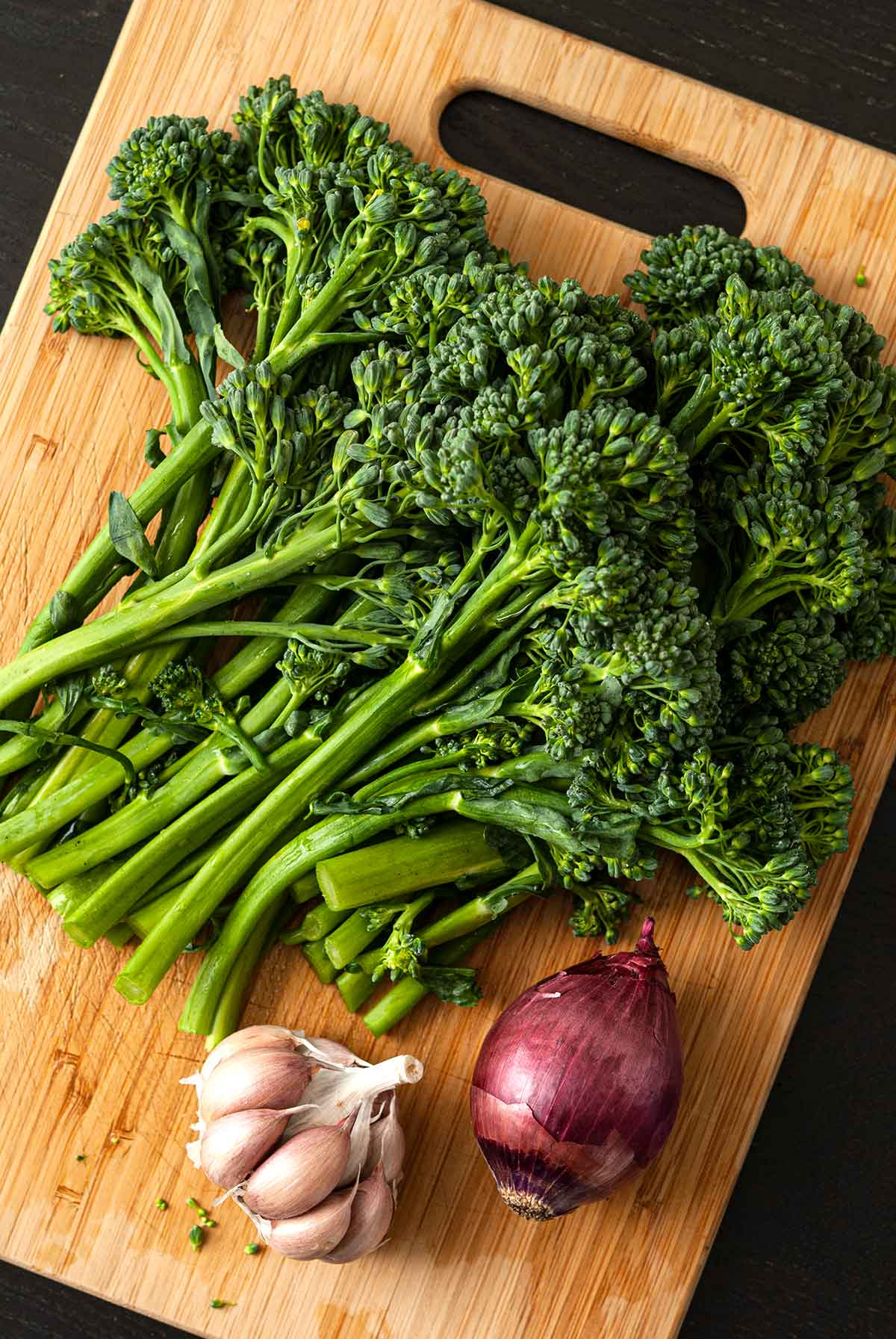 A bunch of raw broccoli rabe on a wooden cutting board with a small red onion and head of garlic.