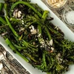 A plate of sautéed broccoli rabe on a lace tablecloth, beside 2 small bowls of garnish.