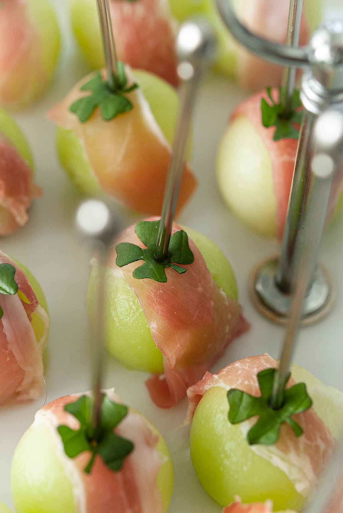 About 10 balled melon appetizers, wrapped in prosciutto with clovers on top, and pierced with cocktail pins.