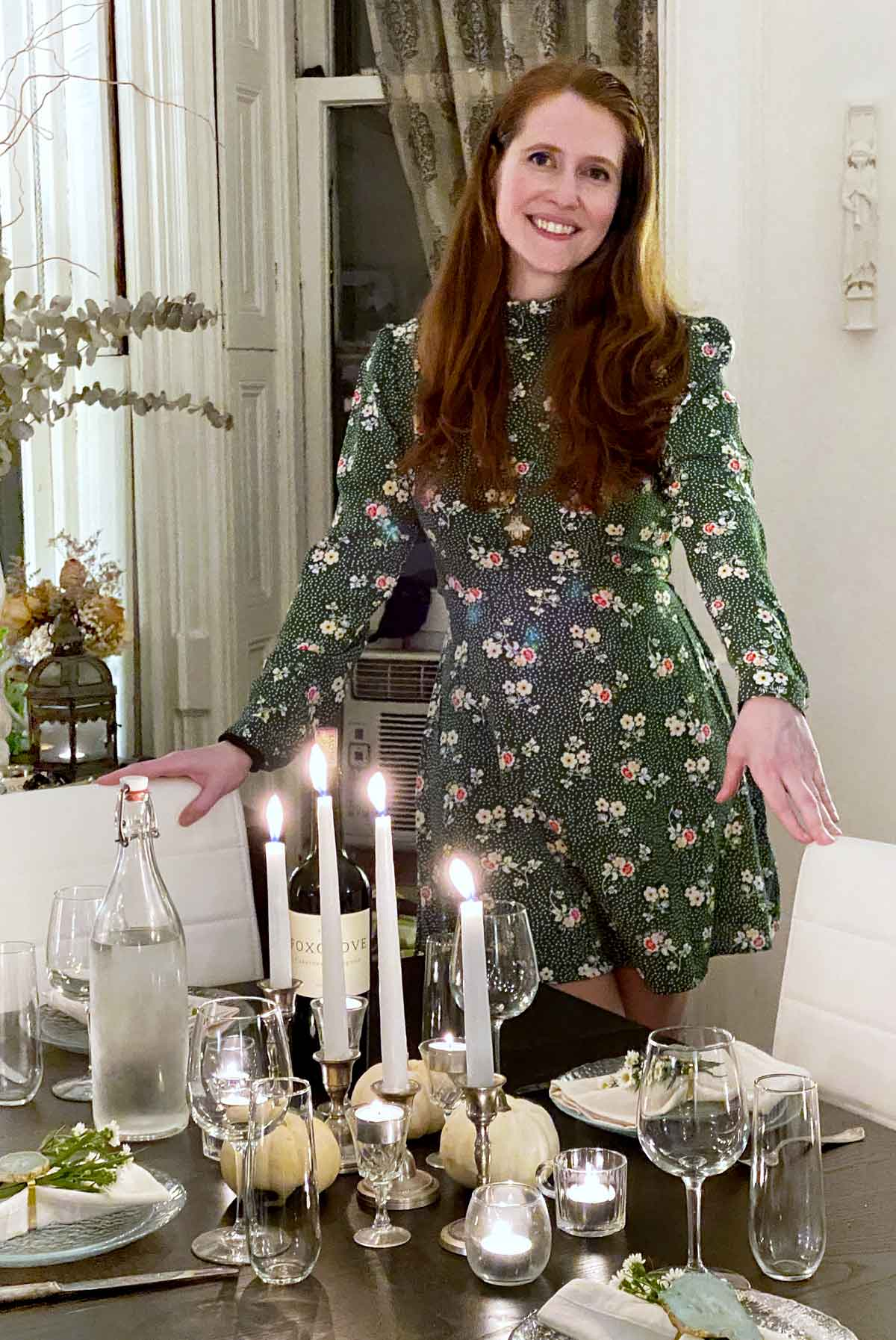 Genevieve Morrison standing at a set dinner table and smiling.