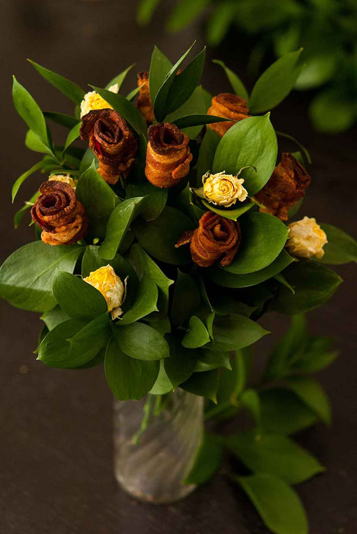 "A ""bouquet"" of bacon roses with leaves and dry, yellow spray roses in a glass vase on a table."