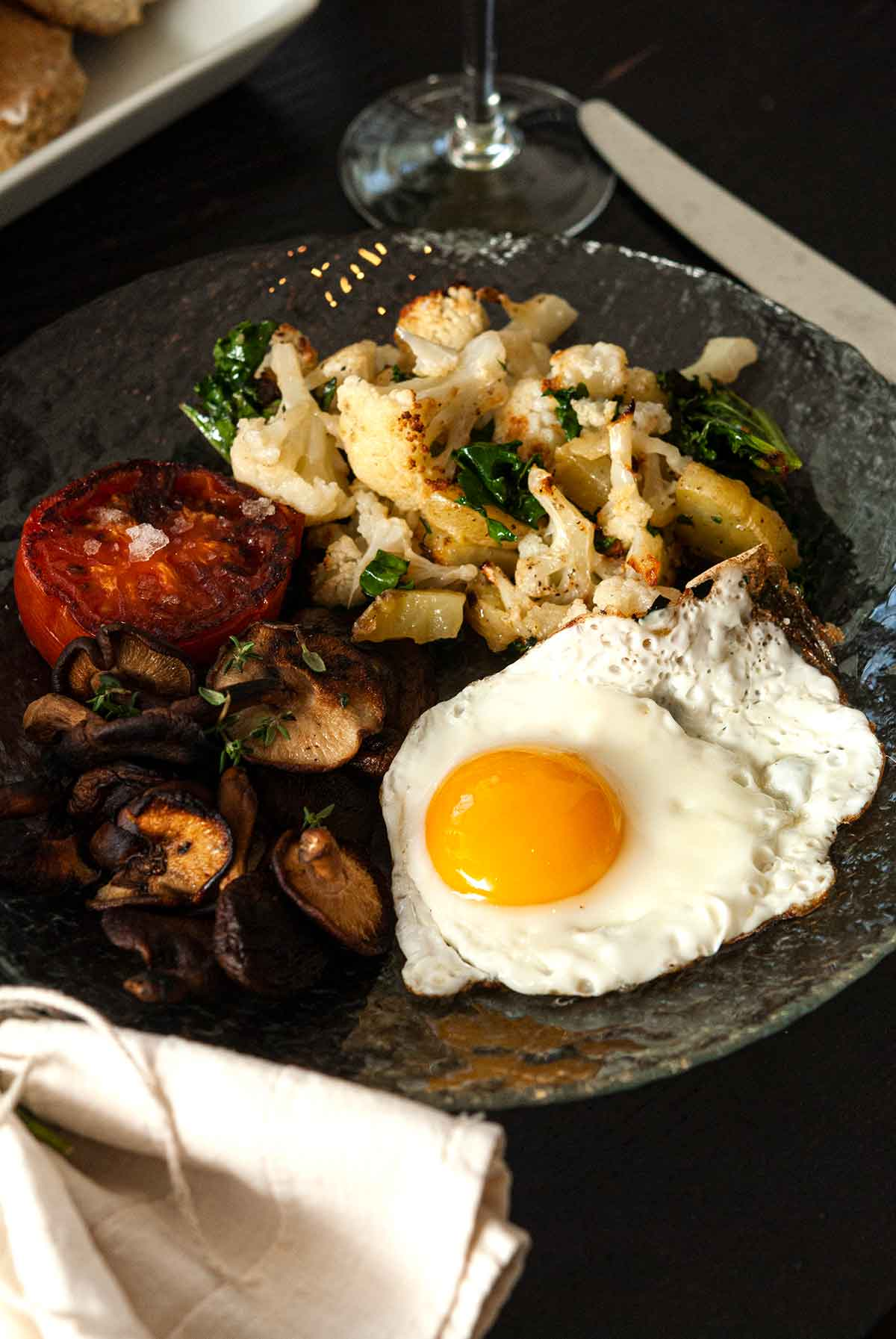 A plate of potato-cauliflower hash, a tomato, mushrooms and 1 egg on a table.