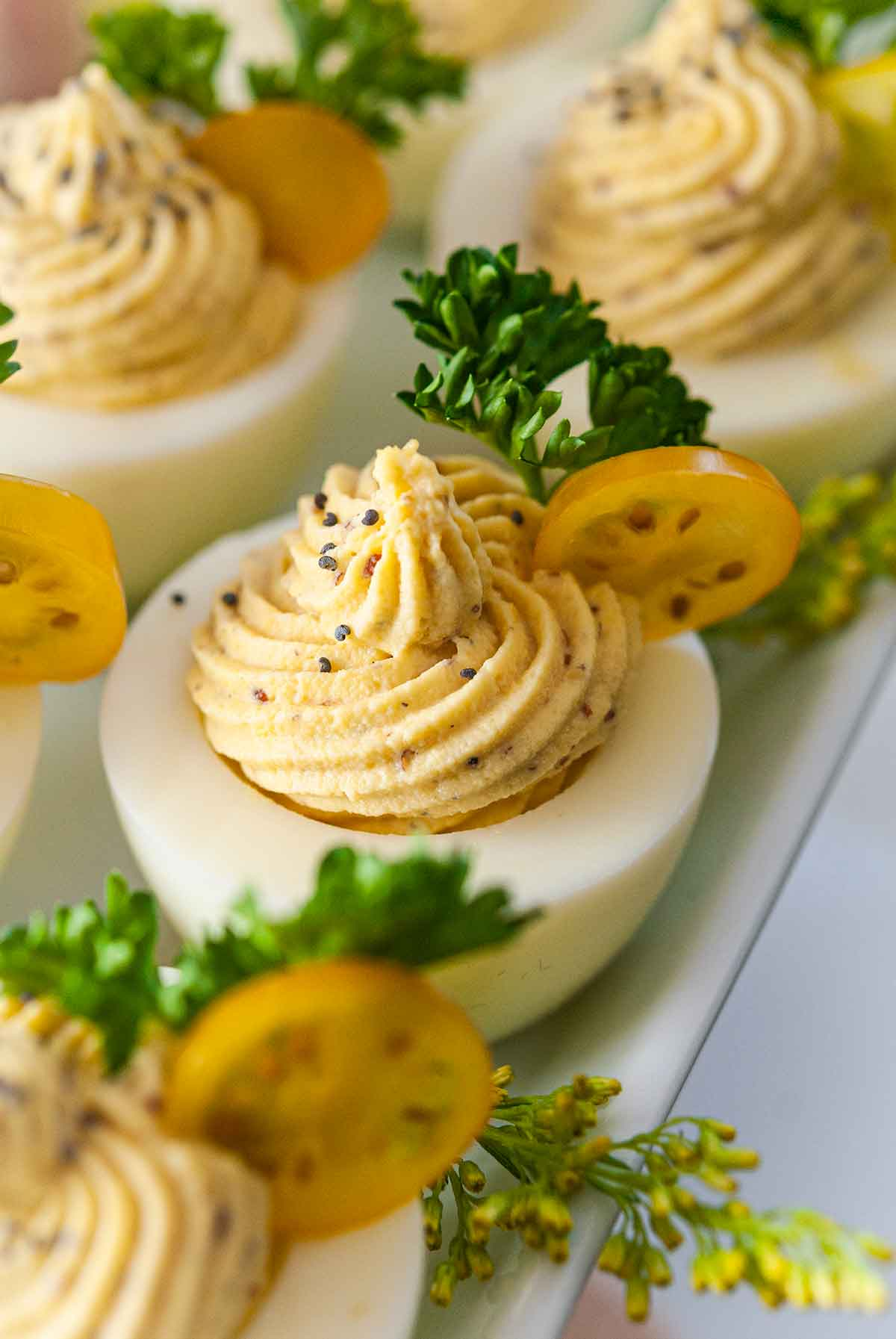 4 deviled eggs on a plate, garnished with tomatoes, parsley and poppyseeds.