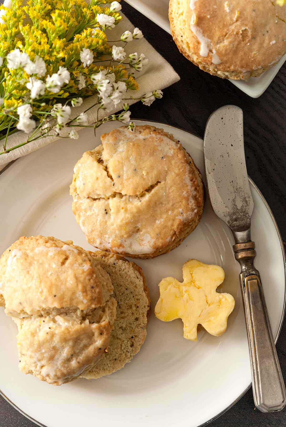 2 scones on a plate with a shamrock-shaped pad of butter, beside a knife, in front of a few flowers o a table.