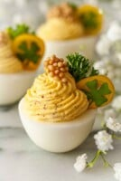 3 deviled eggs, garnished with tomato, clover, parsley and a dollop of mustard caviar on marble.
