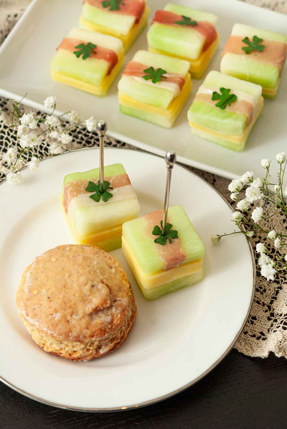 2 melon appetizers on a plate with a scone in front of 6 more melon appetizers on a plate.