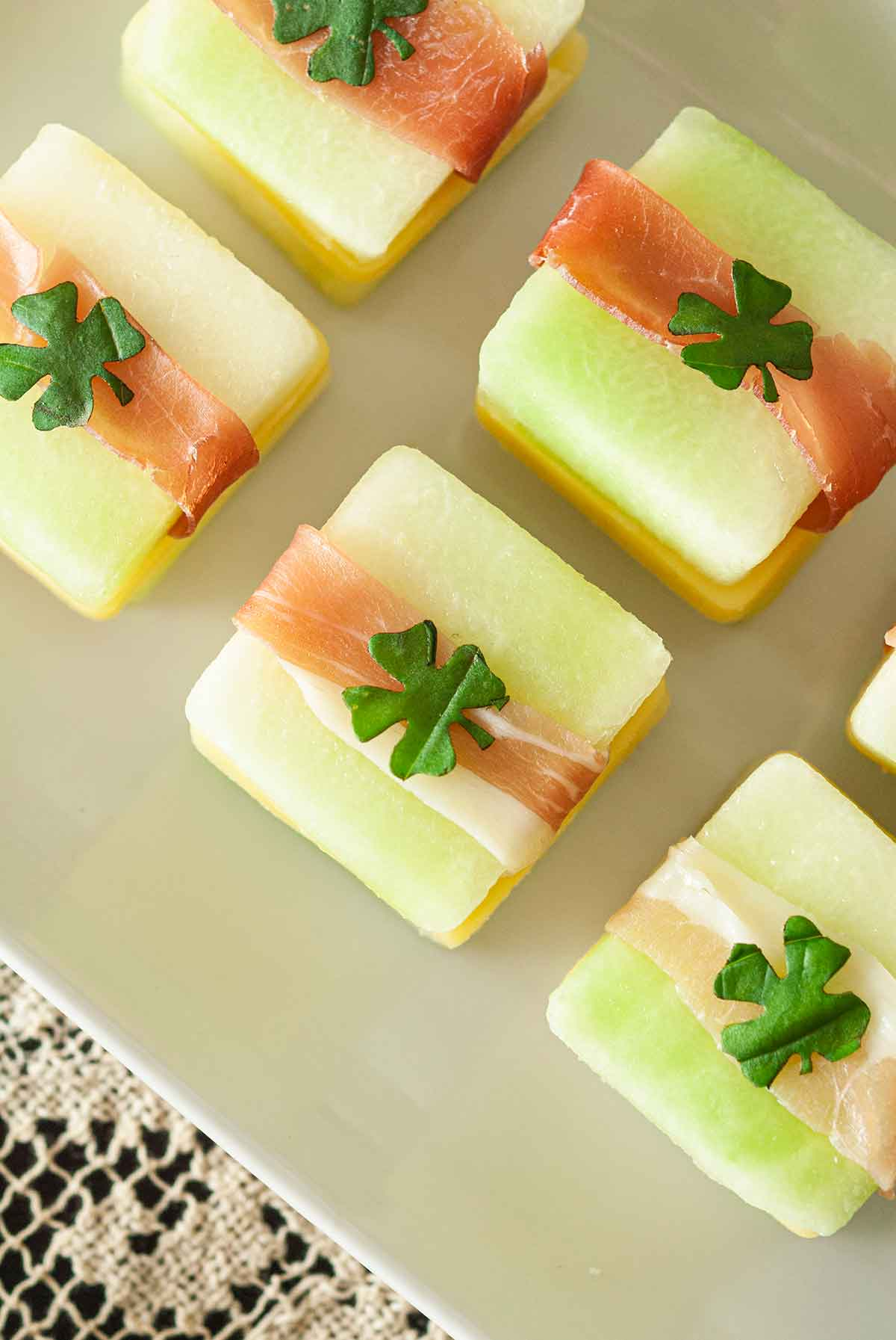 5 St. Patrick's Day melon appetizers with clovers on top, on a white plate.