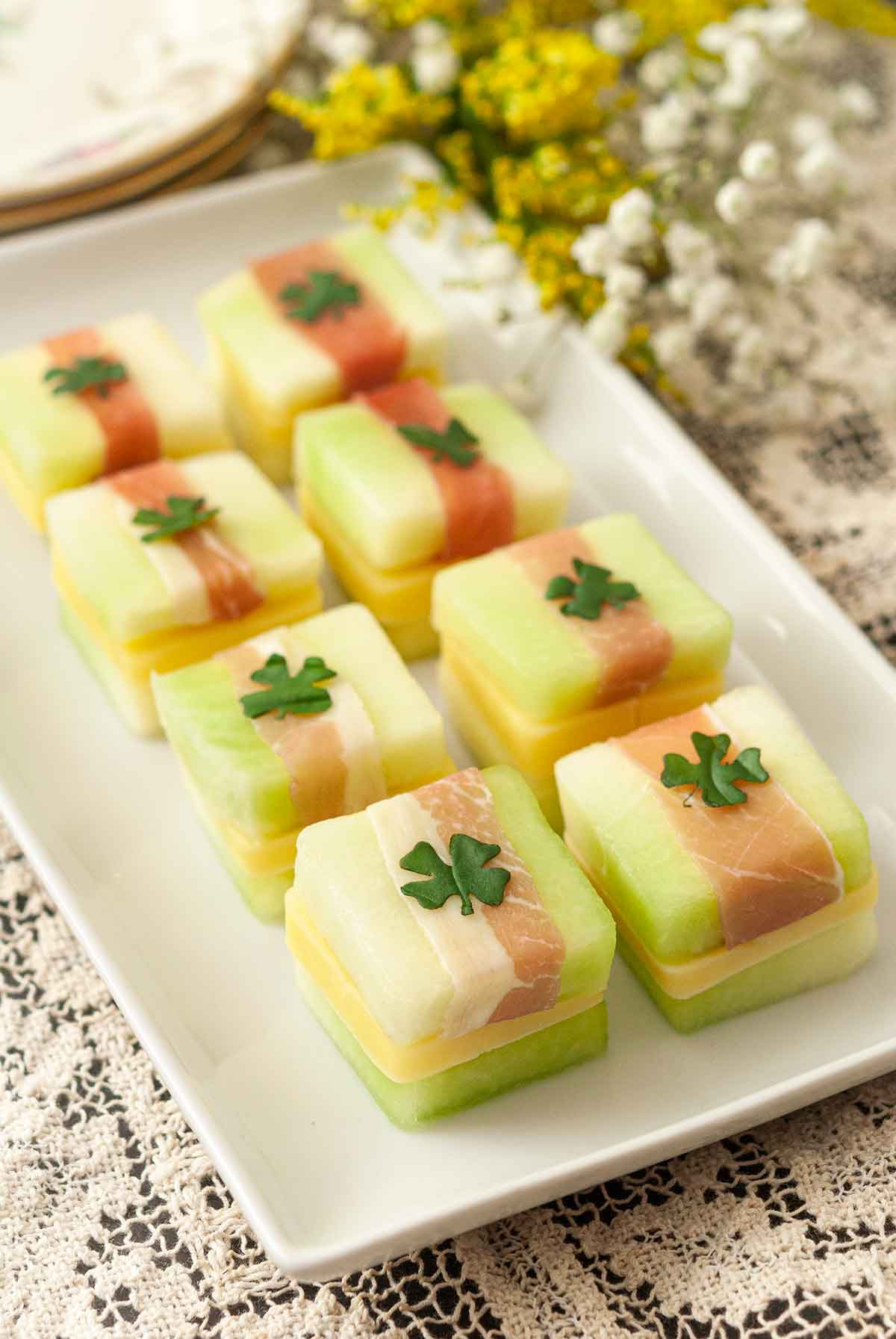8 St. Patrick's Day melon appetizers with clovers on top, on a white plate, on a lace table cloth..