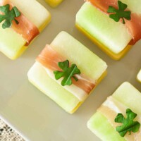 4 St. Patrick's Day melon appetizers with clovers on top, on a white plate.