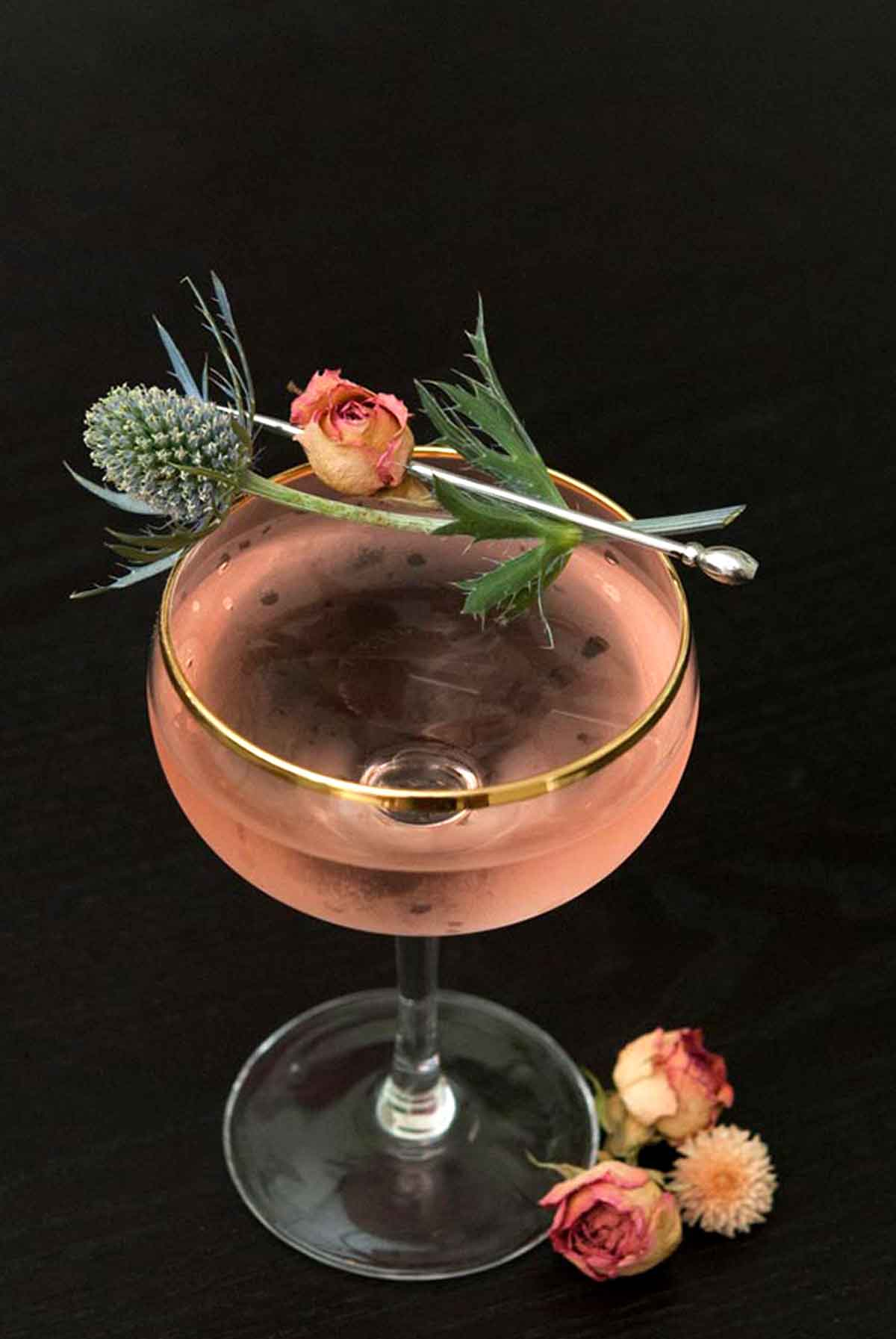 A pink martini, garnished with a pink spray rose and a sprig of thistle on a black table.