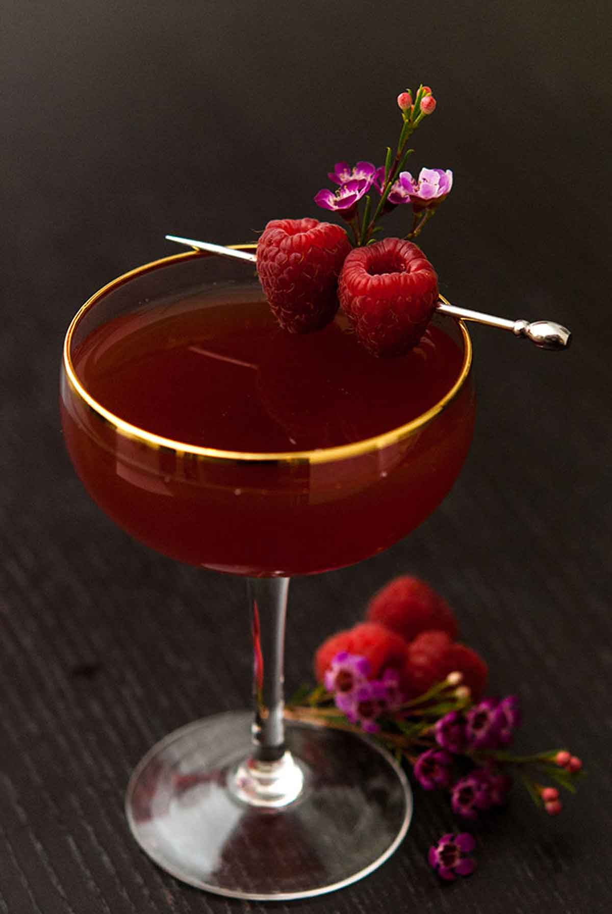 A cocktail on a dark table garnished with raspberries and small flowers, with a few raspberries and flowers at its base.