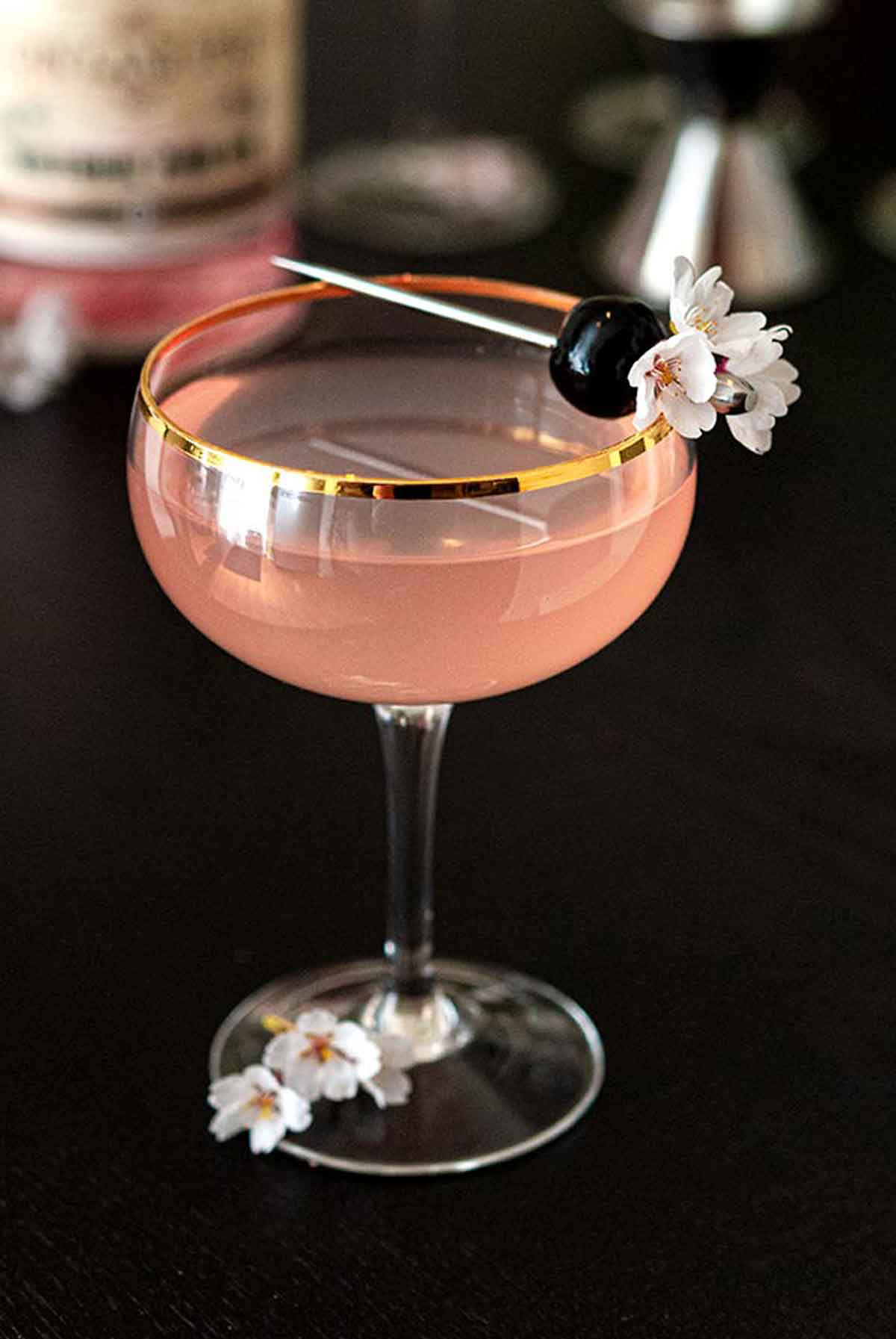 A pink cocktail, garnished with a cherry and small cherry blossoms on a black table.
