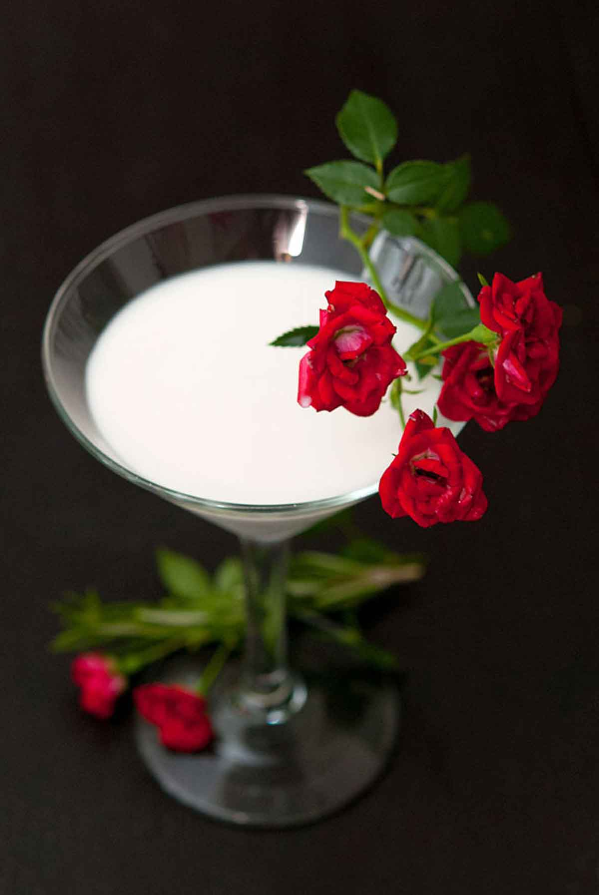 A cocktail in a martini glass on a black table, garnished with a few small spray roses.