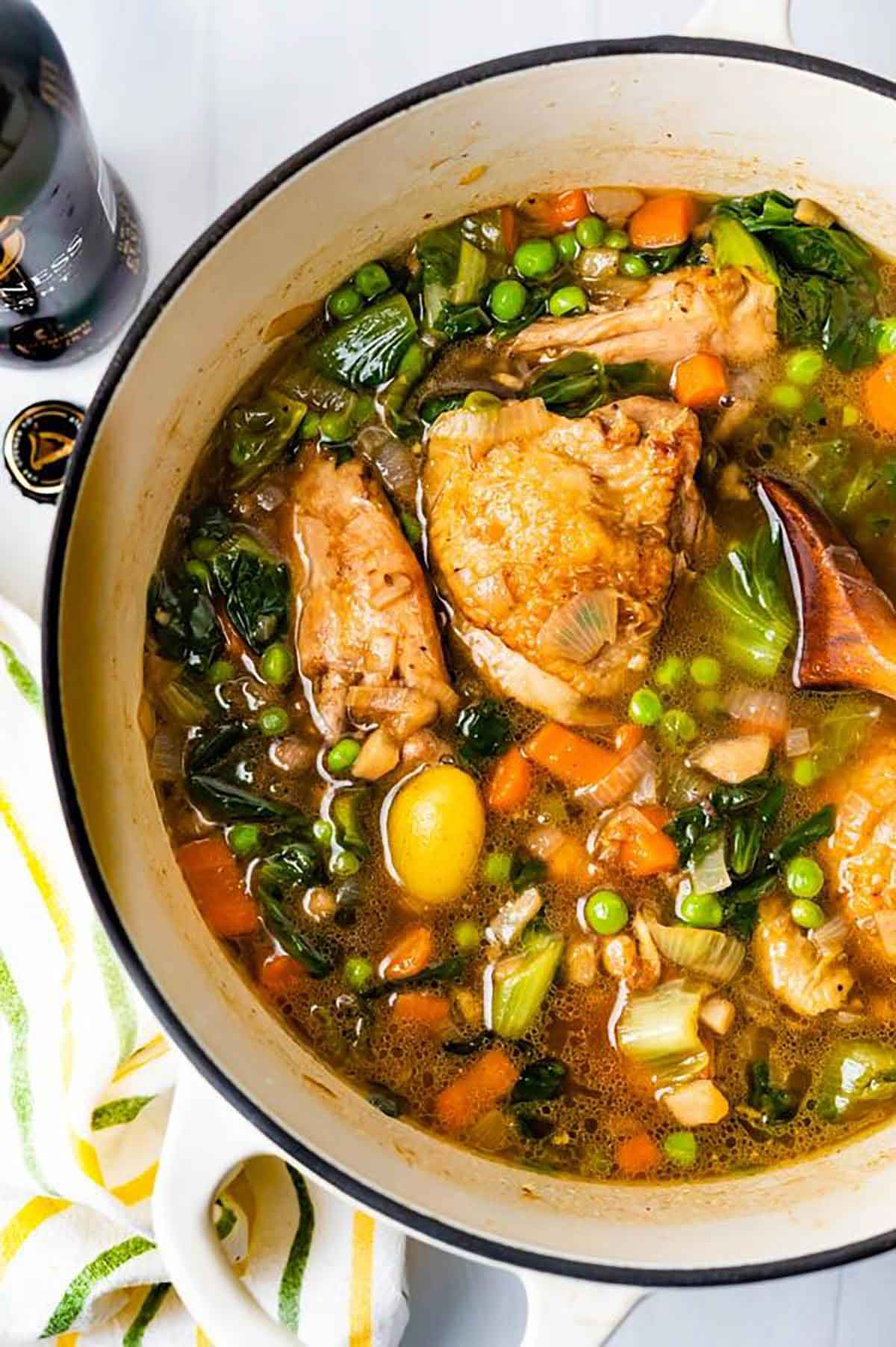 Stout chicken thighs with vegetables in a pot.
