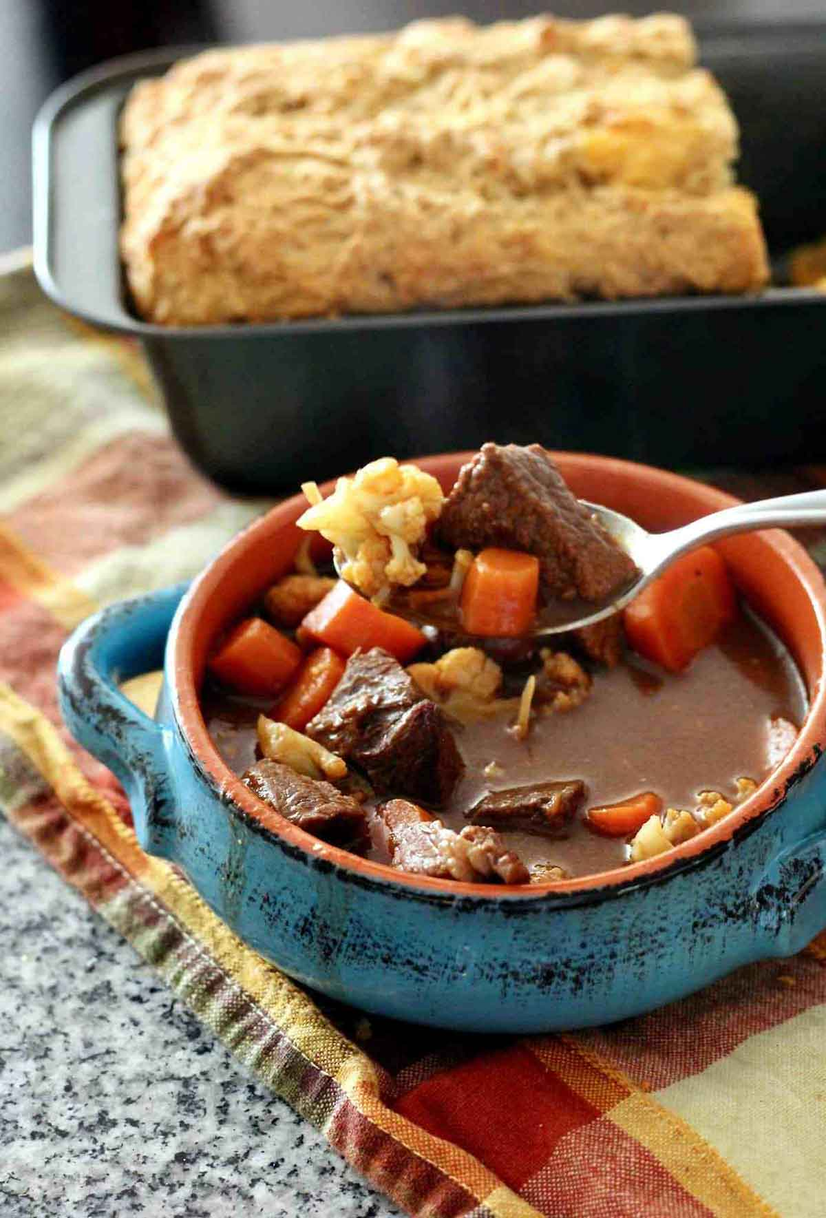 A bowl of beef stew next to a pan of bread.