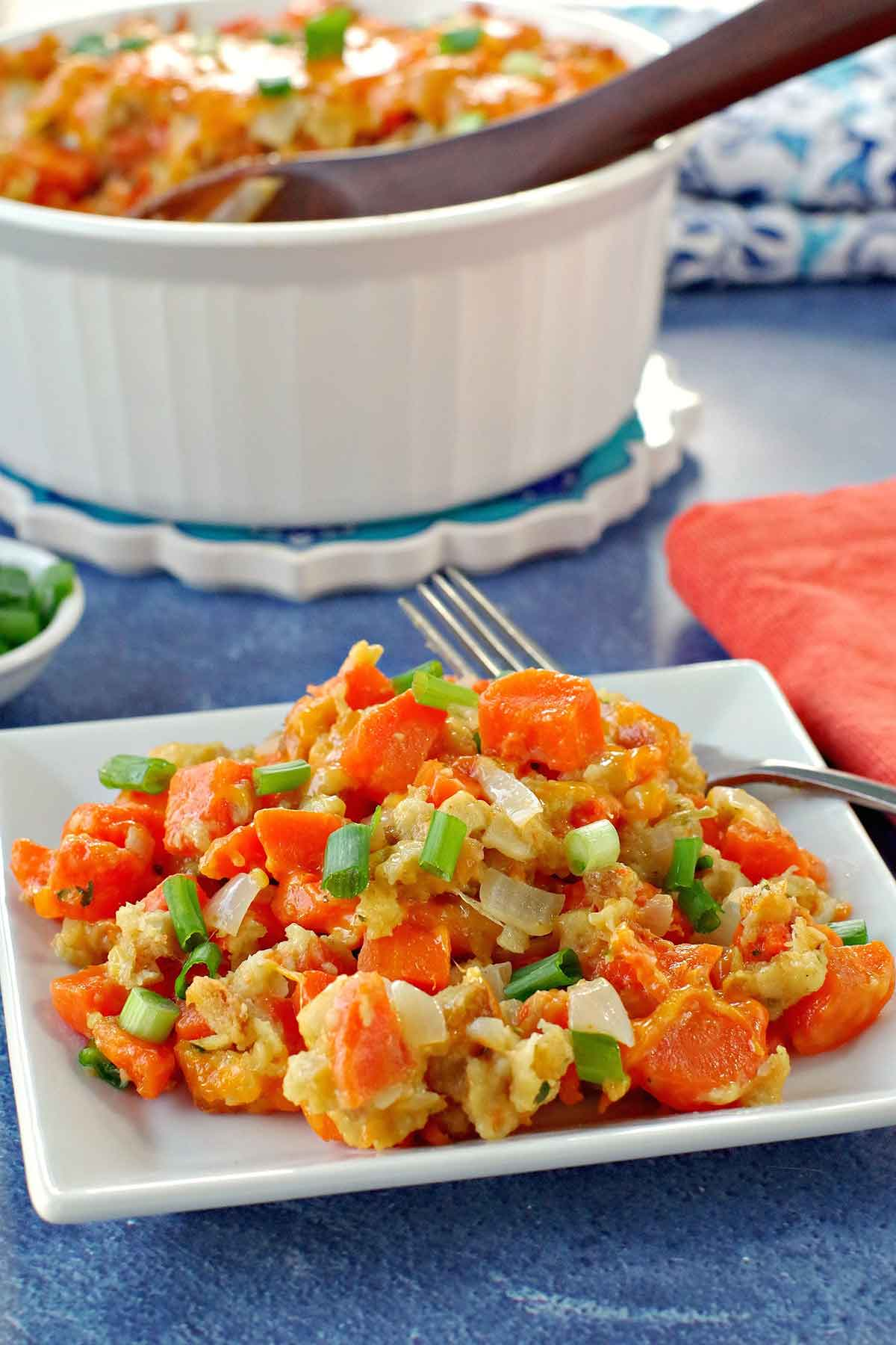 Carrot casserole on a plate with a bowl of casserole in the background.