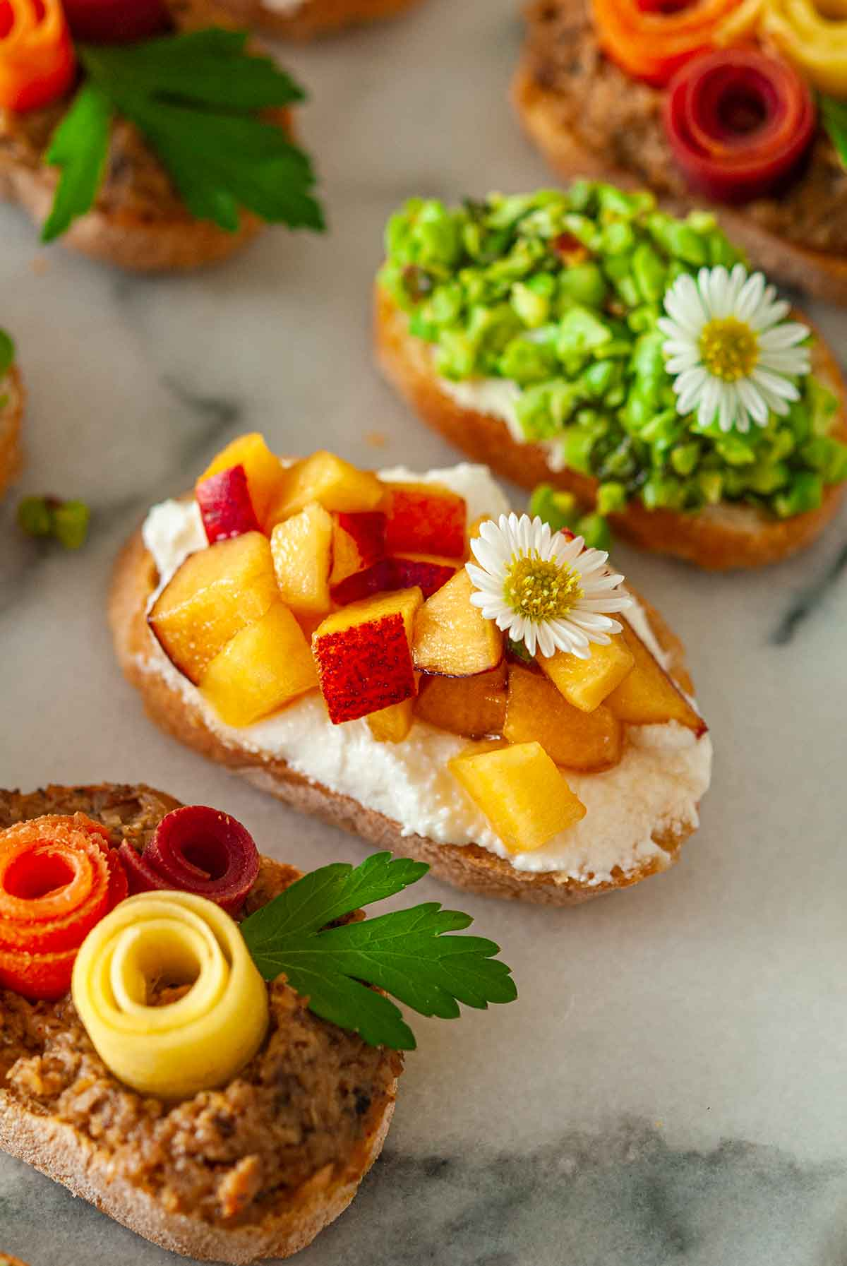 5 brightly colored crostini on a plate, with a peach crostini in the center.