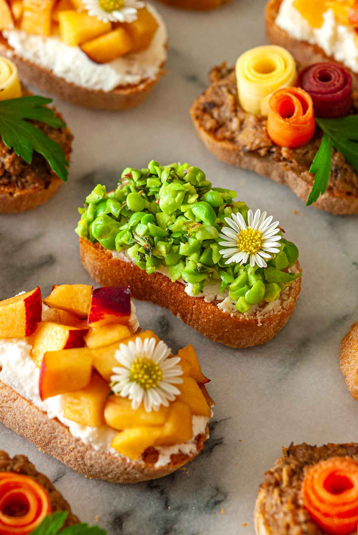 8 brightly colored crostini on a marble slate, with a pea crostini in the center..