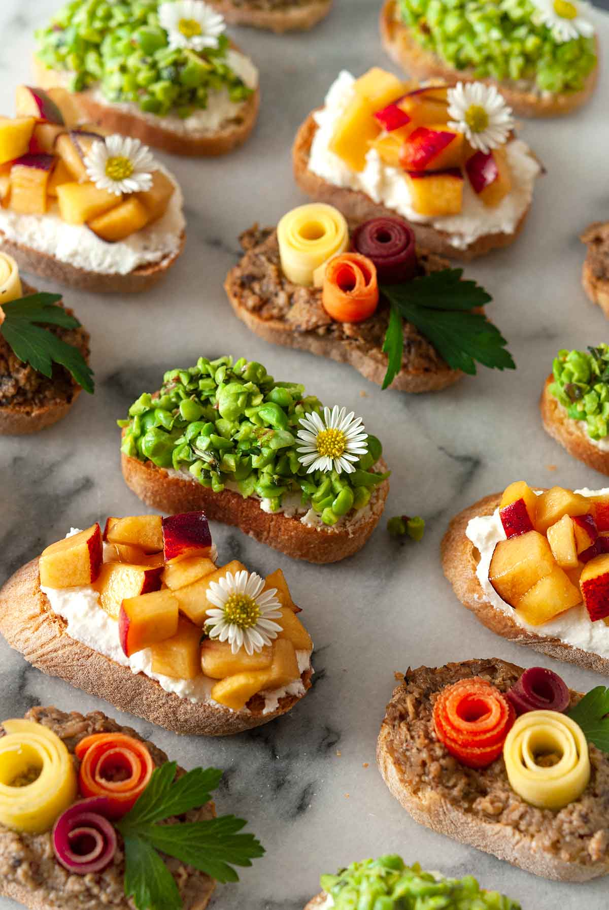 13 beautifully garnished crostini on a marble plate.