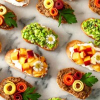 9 brightly colored crostini on a marble slate.