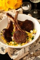 3 seared lamb chops in a bowl with pearl couscous on a table cloth, with flowers in the background.