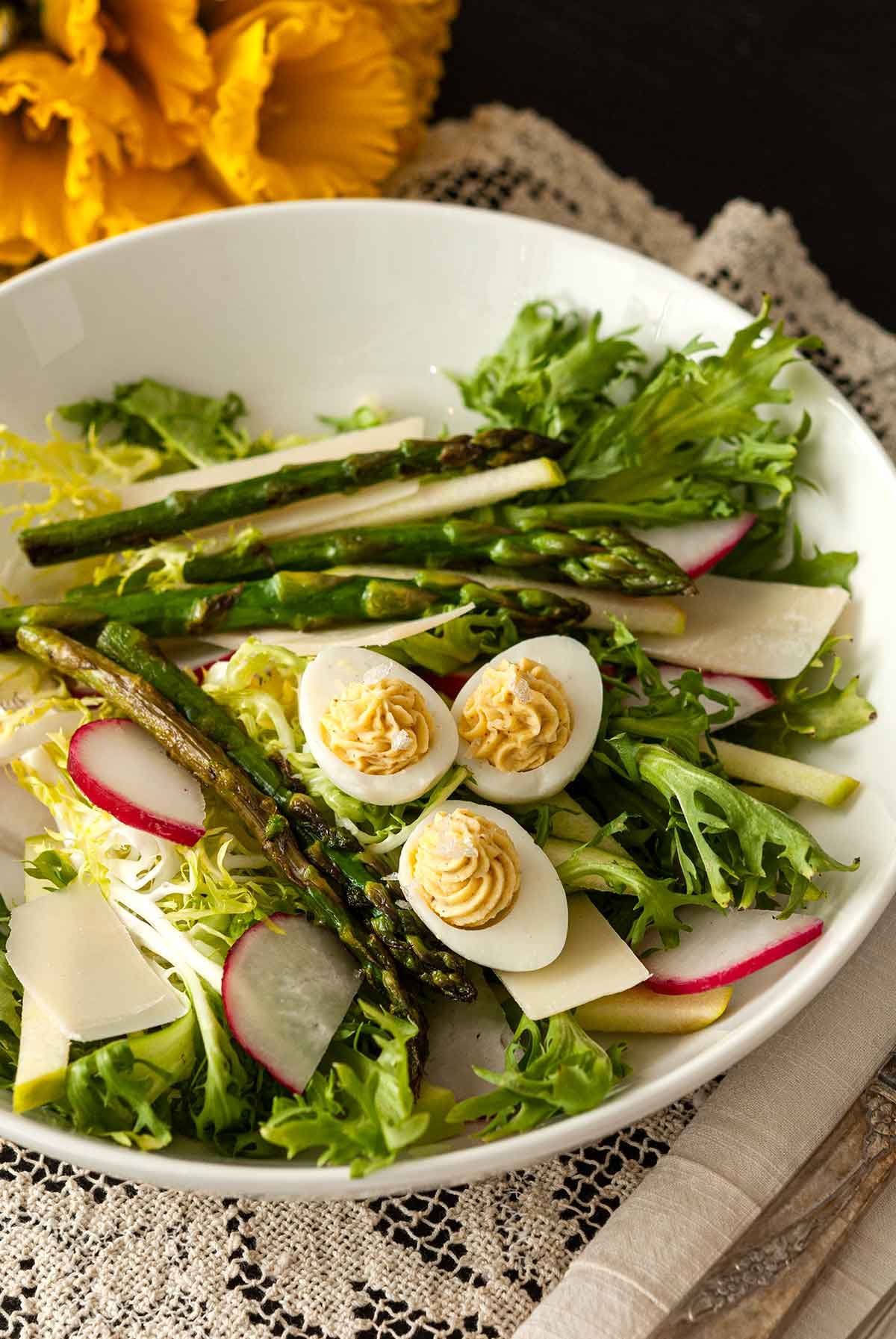 A salad in a bowl on a lace table cloth, topped with small deviled eggs with flowers in the background.