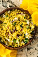 A wooden bowl of turmeric pearl couscous beside flowers on a lace tablecloth.