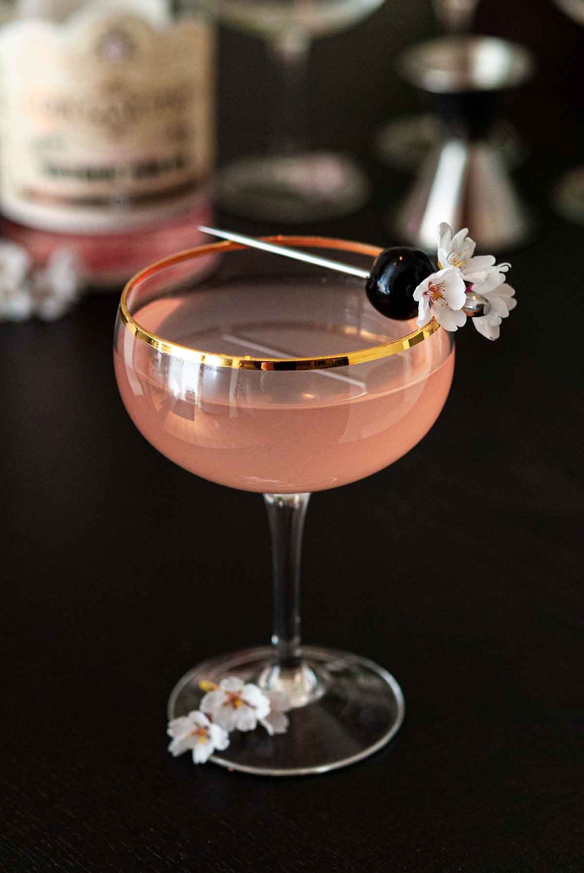 A pink cocktail in a coup glass, garnished with a cherry and flowers, on a table.