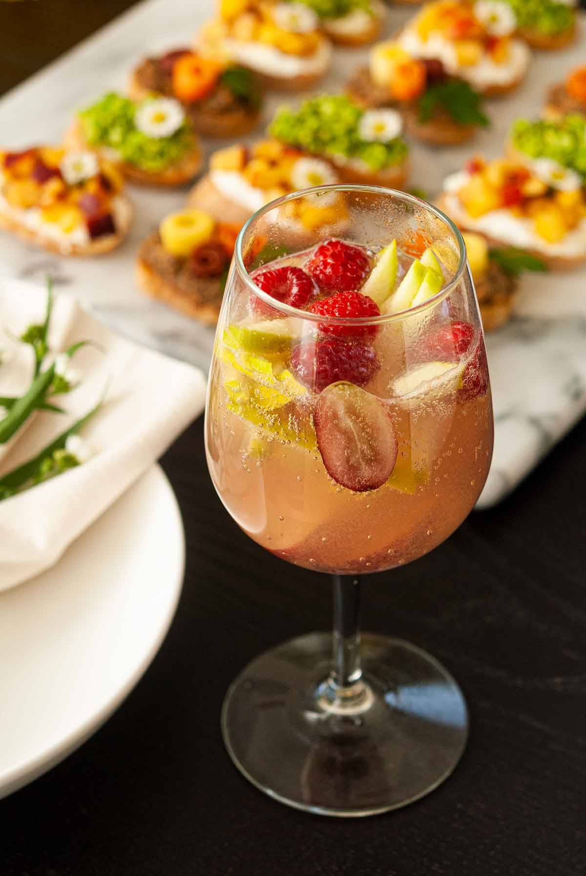 A glass of sake sangria, full of fruit, on a table beside appetizers.
