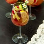 A glass of sake sangria, full of fruit, beside a lace table cloth.