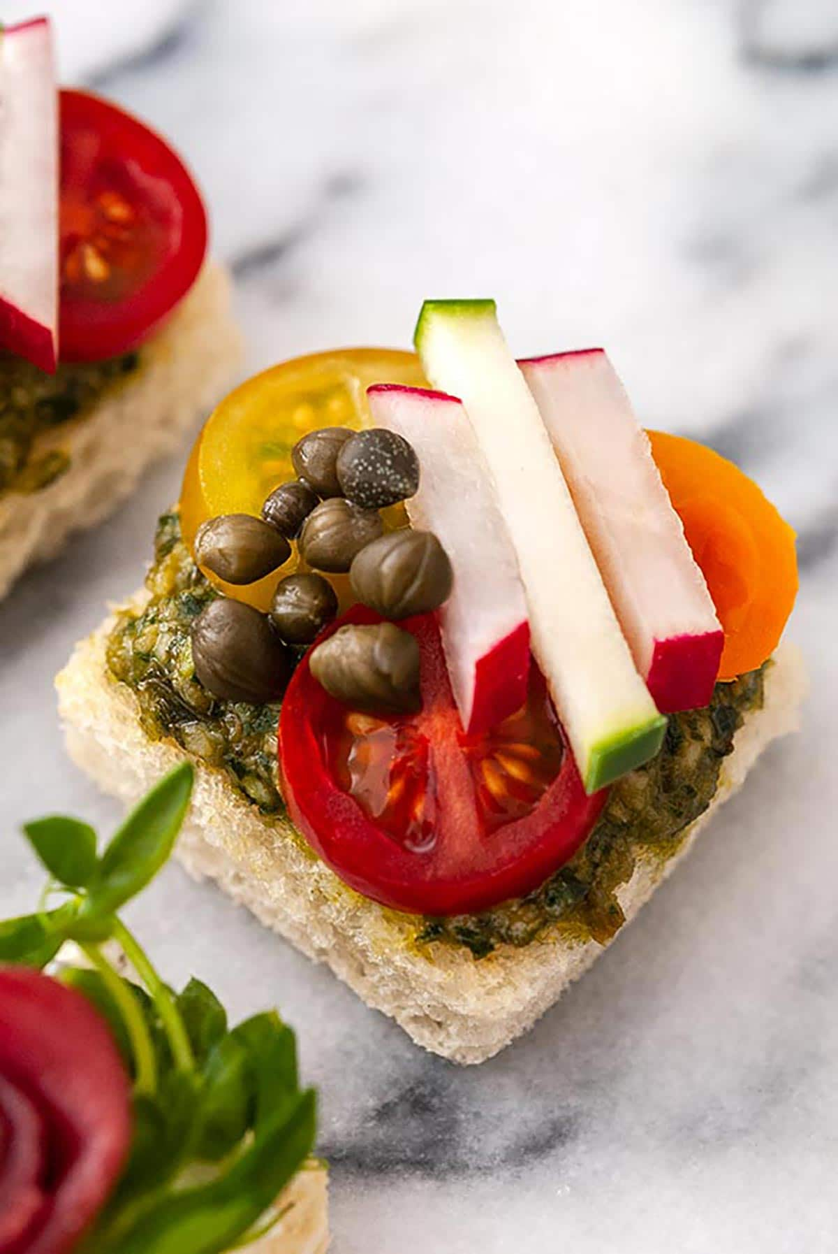 A canapé with tiny cut vegetables and capers on a marble tray.