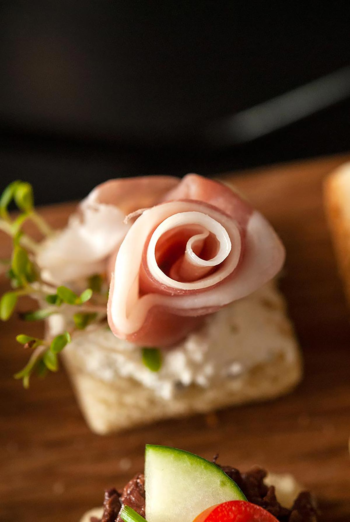 A canapé with a prosciutto rose.