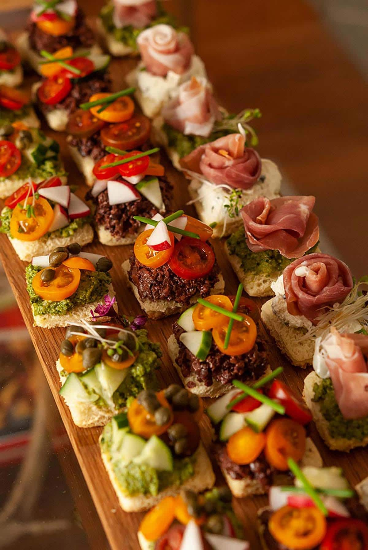 An appetizer tray of 24 canapés in 3 different styles.