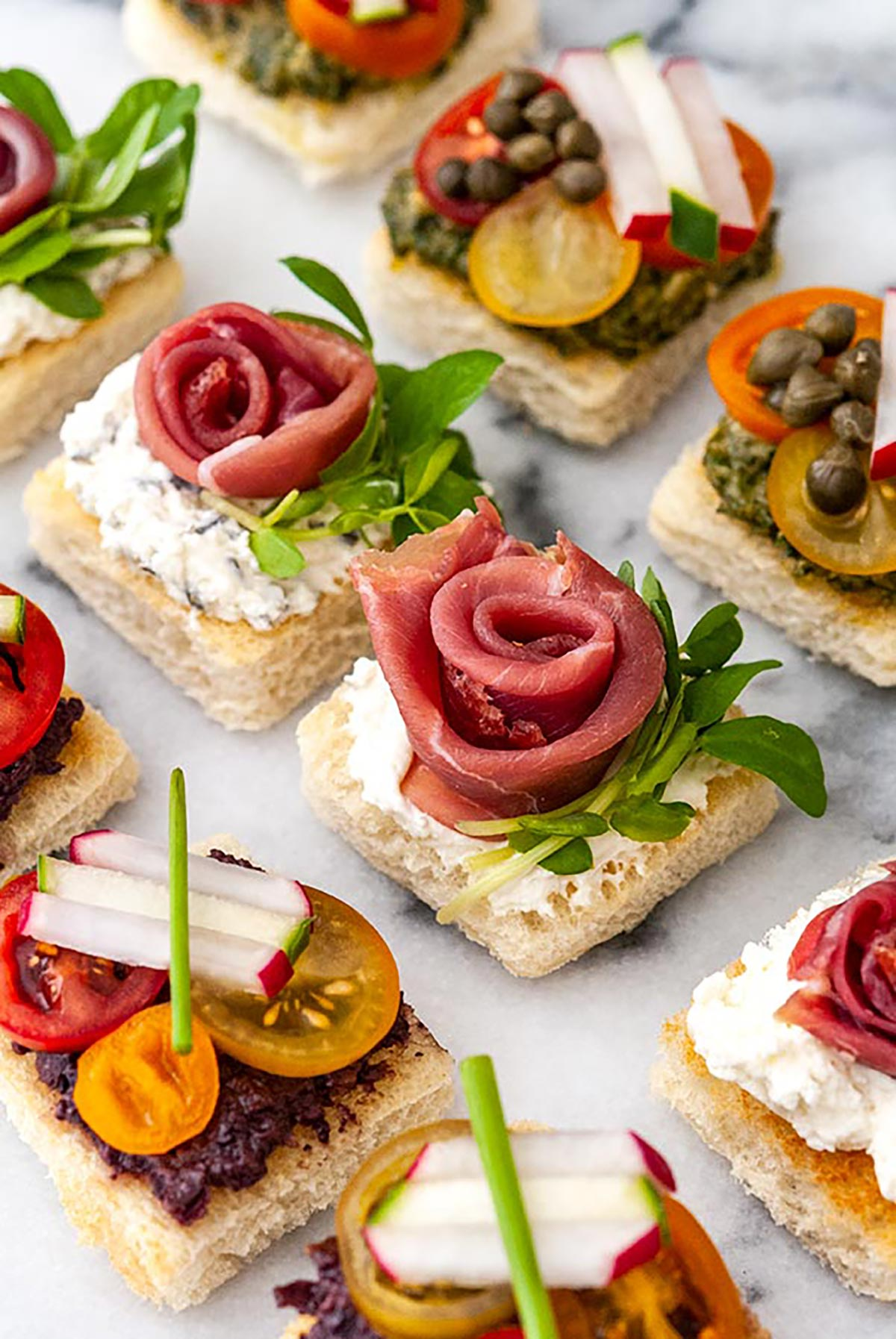 A marble appetizer tray of 9 canapés in 3 different styles.