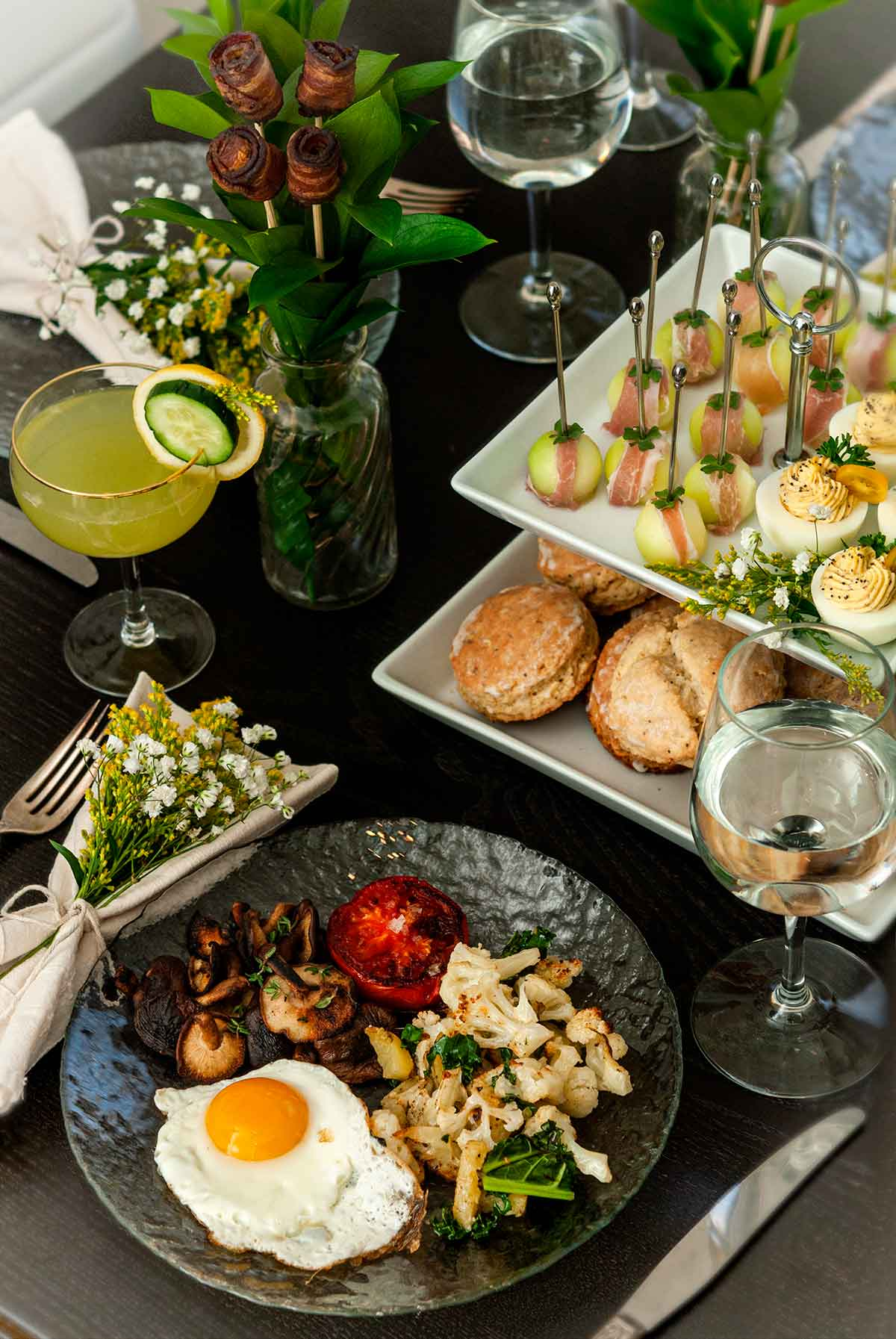 An ornately decorated table with breakfast foods, glasses of water and cocktails.