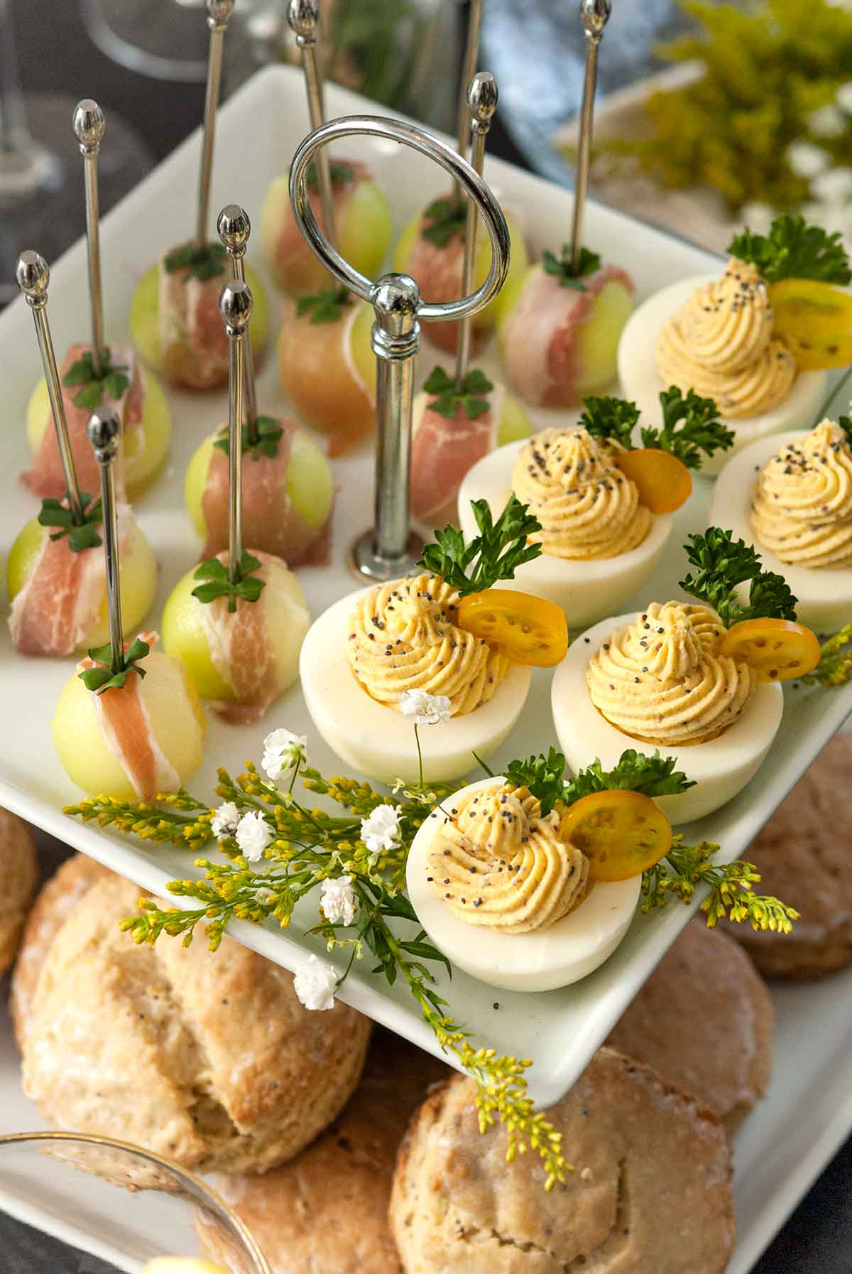 An appetizer tier with deviled eggs and prosciutto-wrapped melon above scones on a table.