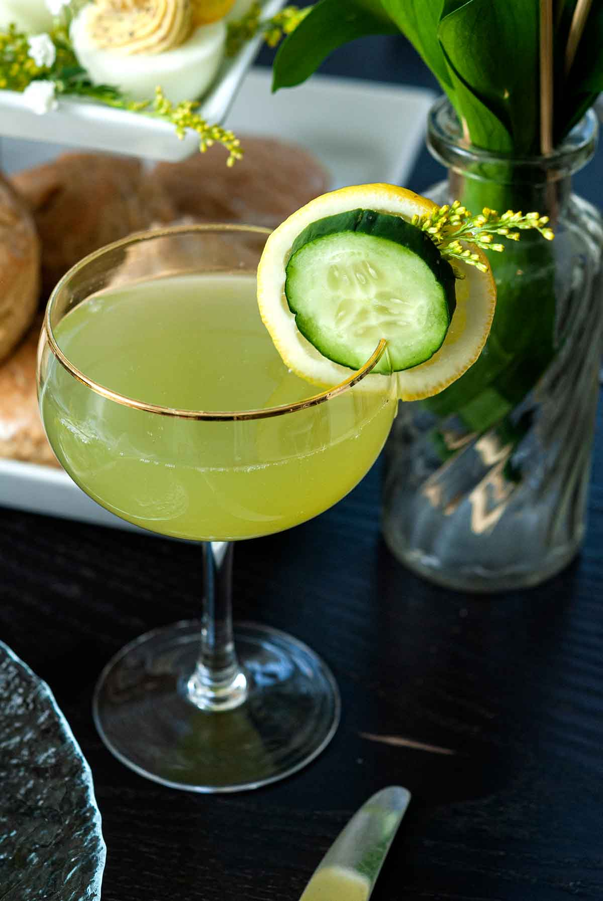 A cocktail garnished with cucumber and lemon on a table in front of a tier of sones and deviled eggs.