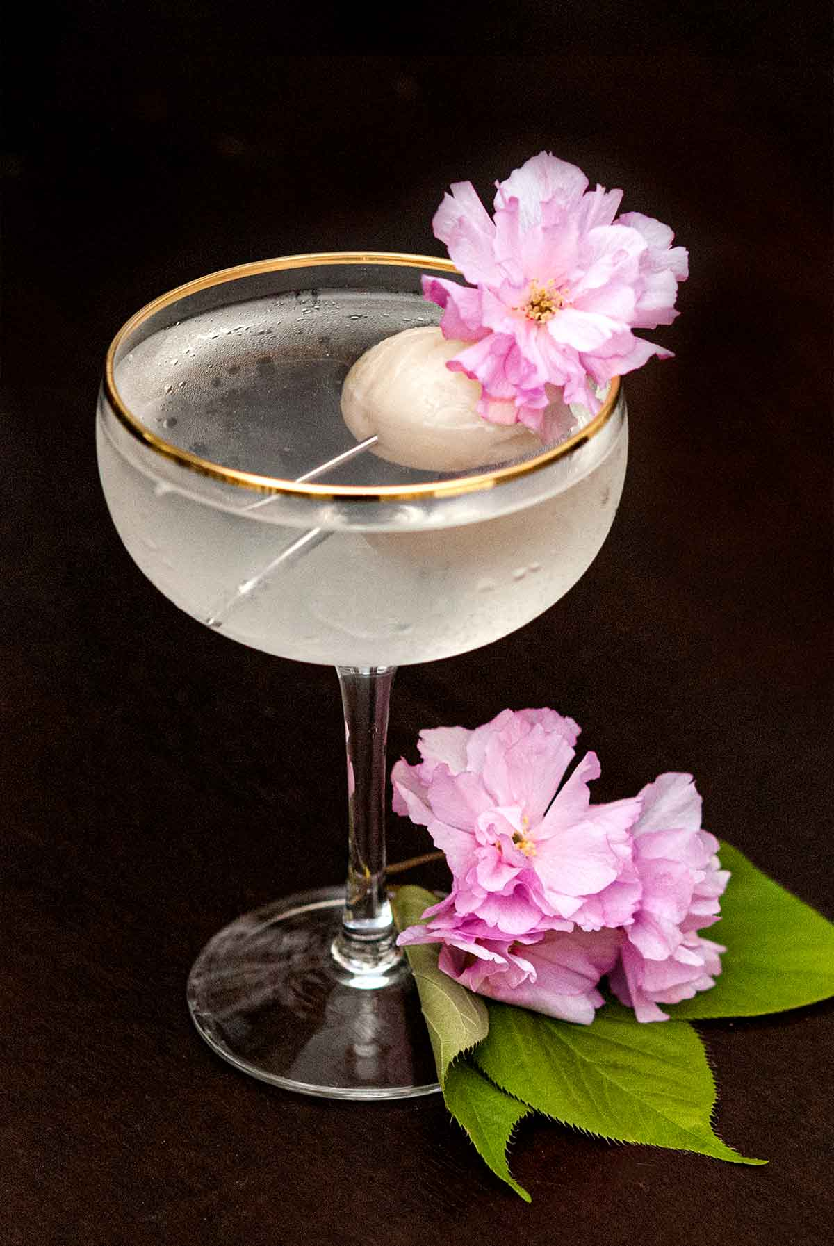 A cocktail garnished with a lychee and cherry blossom flowers, with flowers and a few leaves at its base.