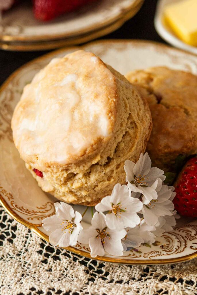 The glaze on one of 2 scones on a plate with flowers.