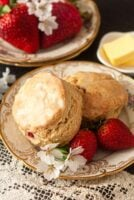 2 scones on a decorative plate with flowers and strawberries, in front of stacked plates and more strawberries.