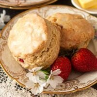 2 scones on a decorative plate with flowers and strawberries.