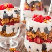 3 parfaits with berries, granola and cream on a table.