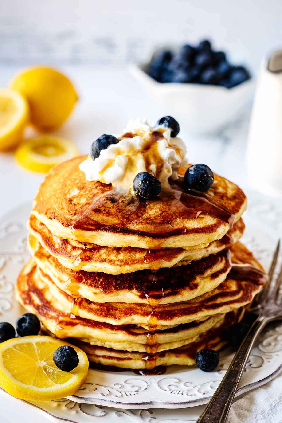 A stack of pancakes topped with cream and blueberries, with slices in the backgroun.