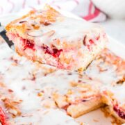 A spatula holding up a strawberry cheesecake danish above a full danish in a baking dish.