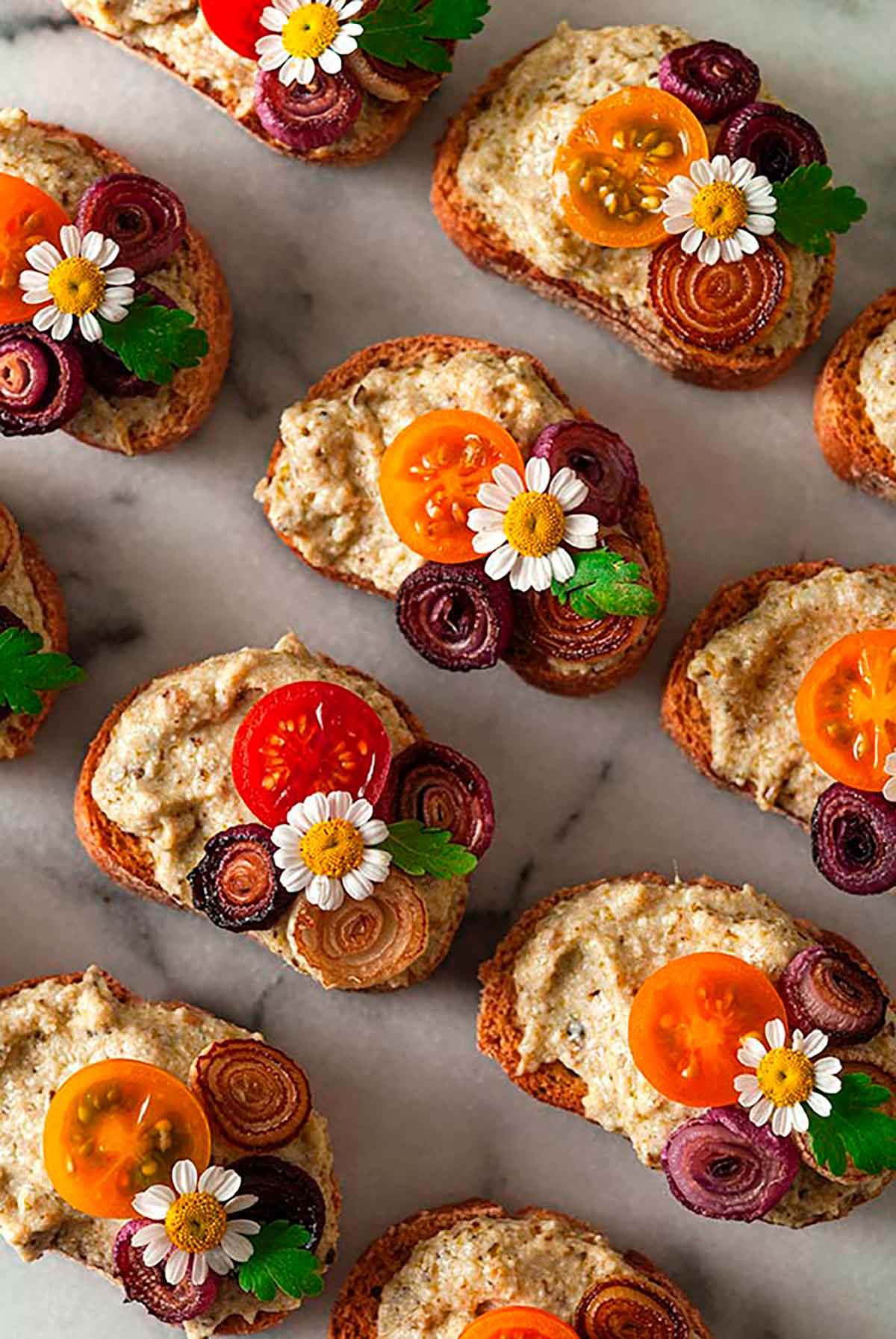 Crostini garnished with daisies, onions and tomatoes on a marble plate