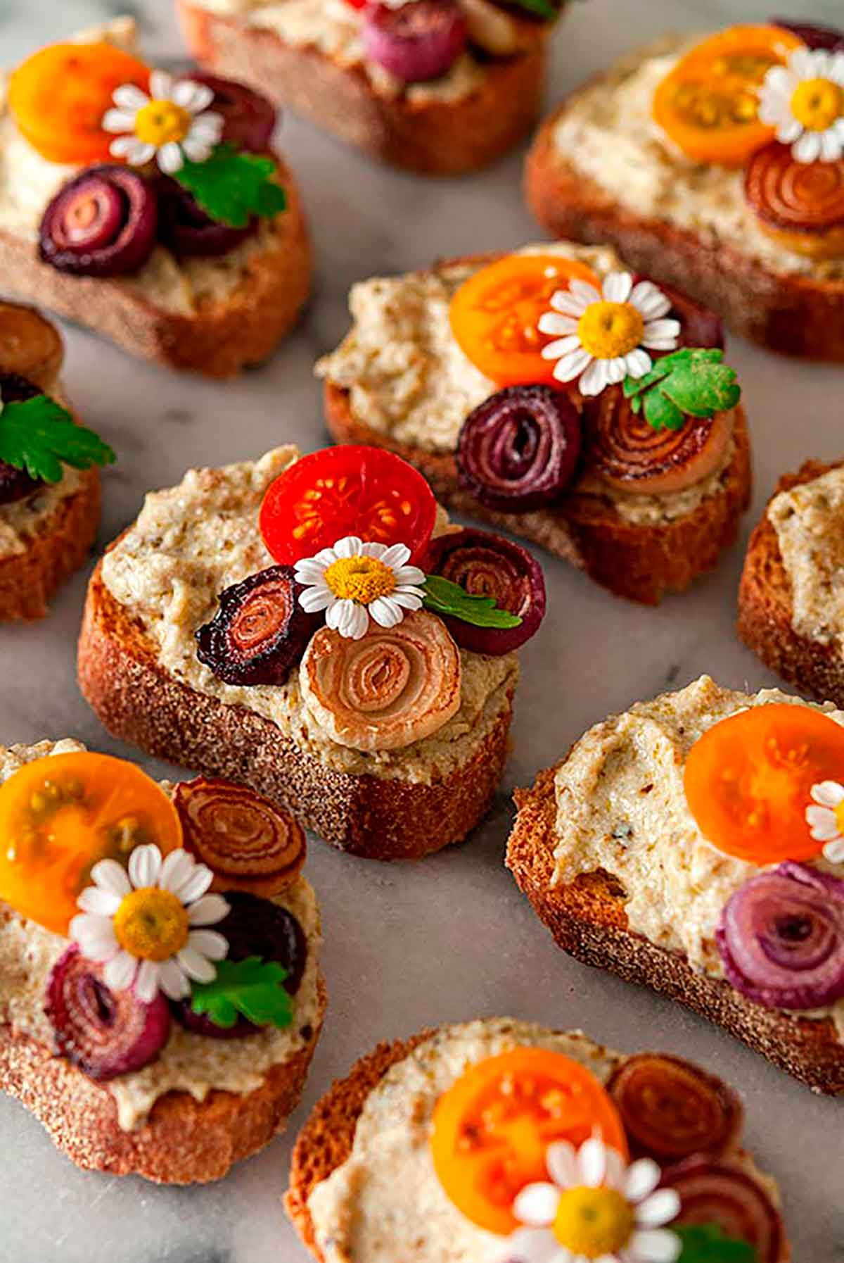 11 crostini garnished with daisies, onions and tomatoes on a marble plate.